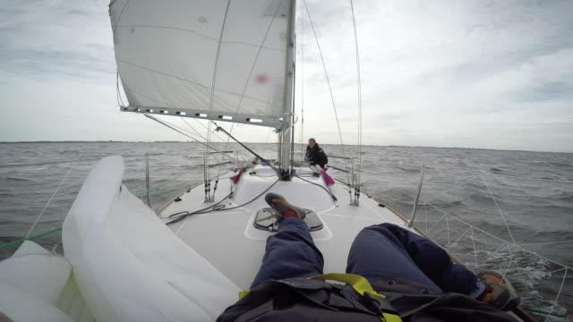 women in sport: female solo sailor, filmed by friend - marinaio video stock e b–roll