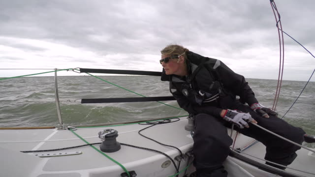 women in sport: female solo sailor keeping an eye out - potere femminile video stock e b–roll