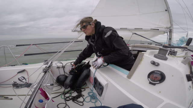 women in sport: female solo sailor preparing for docking - matrose stock-videos und b-roll-filmmaterial