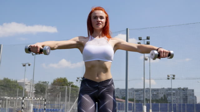 women in sport. redhead fitness woman training with dumbbells on open air - sports commentator stock videos & royalty-free footage