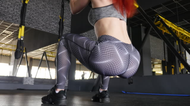 women in sport. redhead fitness woman training with trx fitness straps - commentator stock videos & royalty-free footage