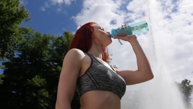 Frauen im Sport & junge schöne Mädchen ist Trinkwasser im Park in der Nähe des Brunnens