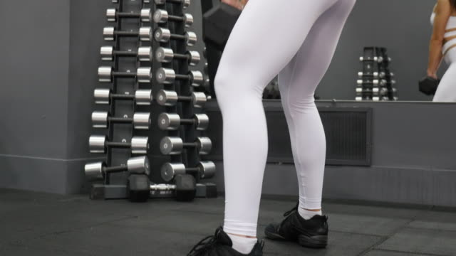 Frauen im Sport. Junges schönes Mädchen engagiert sich für ein Fitnessgerät im Fitness-center