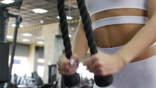 frauen im sport. junges schönes mädchen engagiert sich für ein fitnessgerät im fitness-center - 20 24 years stock-videos und b-roll-filmmaterial