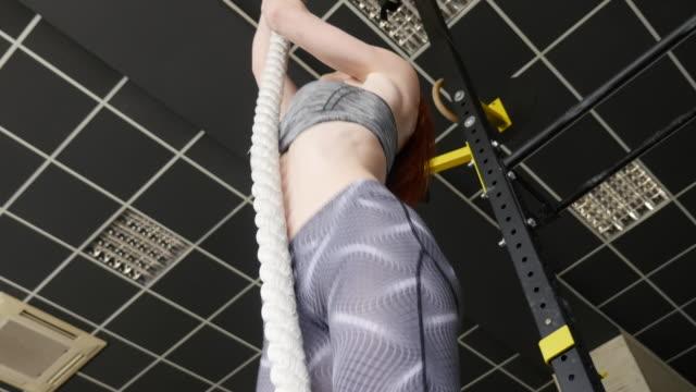 Frauen im Sport. Junges schönes Mädchen engagiert sich an einem Seil im Fitness-center
