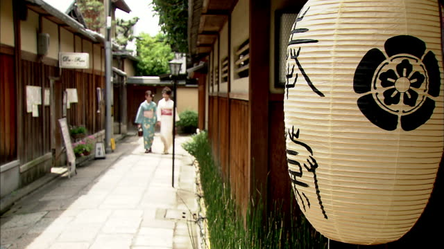 Women in summer kimonos walk through an alley, followed by women carrying shopping bags.