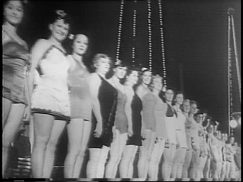 vidéos et rushes de women in swimsuits and high heels circle stage as contestants / husbands and children cheer from reserved area, sign reads 'hubbies cheering section'... - concurrent
