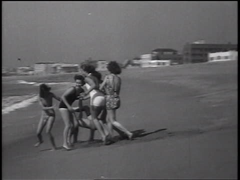 b/w 1937 pan women in swimsuits carrying other woman + throwing her into surf / newsreel - 水かけっこ点の映像素材/bロール