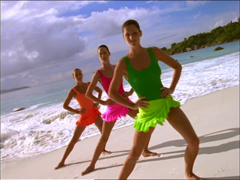 3 women in swimsuits doing aerobics on beach / Seychelles