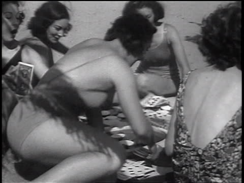 B/W 1937 women in swimsuits fighting as one woman tries to take chips in card game on beach / news.
