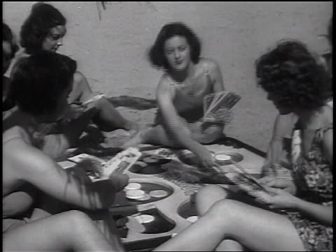 b/w 1937 women in swimsuits playing cards on blanket on beach / newsreel - 1937 stock-videos und b-roll-filmmaterial