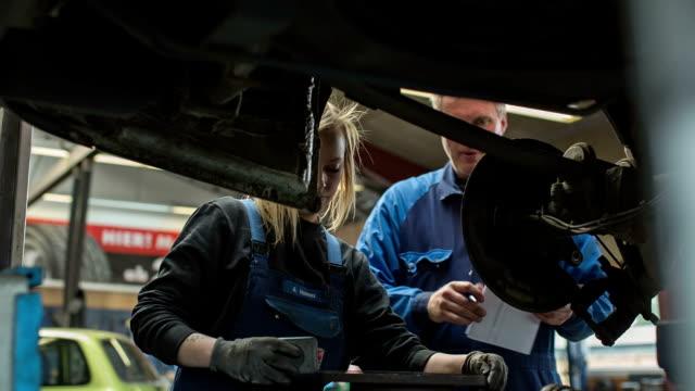 women in technology - a girl as an apprentice in a car repair shop - frauenrechte stock-videos und b-roll-filmmaterial