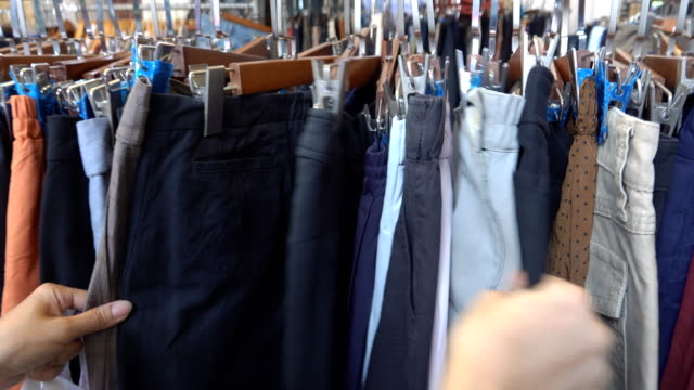 vídeos de stock e filmes b-roll de women in the store choosing jeans hanging on racks - calças