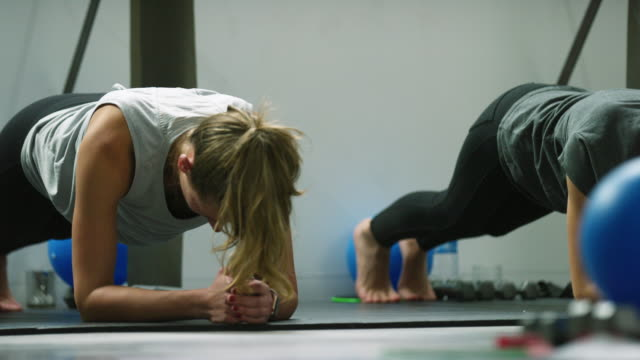 women in their twenties in plank position at an exercise studio - barre stock videos & royalty-free footage