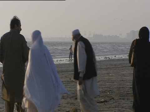 women in veils and men walk along the beach in karachi - karachi stock videos and b-roll footage