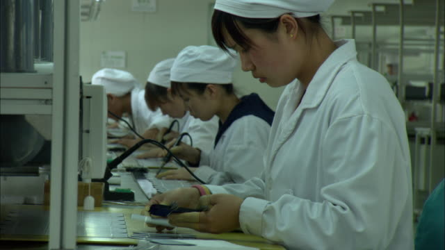 cu zo ms women in white coats soldering parts used to make solar hot water heaters, dezhou, shandong, china - arbeitsintensive produktion stock-videos und b-roll-filmmaterial