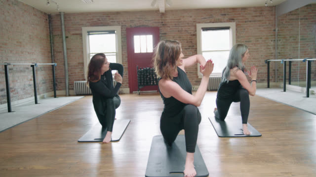 women in yoga warrior pose - barre fitness stock videos and b-roll footage