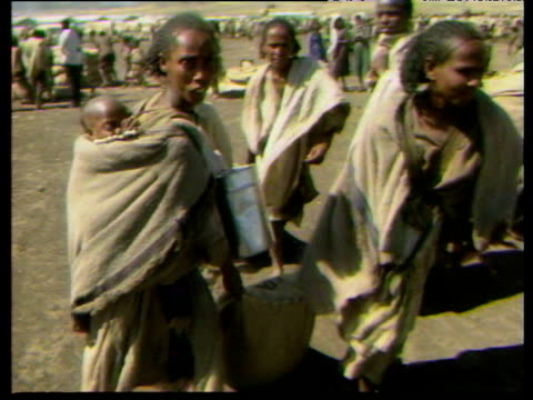 Women including one carrying baby dragging sack of grain during Ethiopian famine Oct 84