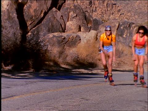 2 women inline skating toward camera on desert road / high five - blade stock videos & royalty-free footage