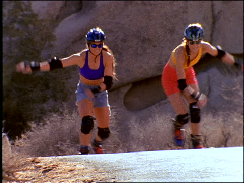2 women inline skating toward camera on desert road / tilt down to feet