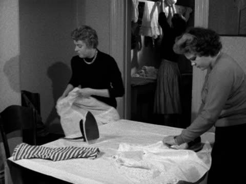 vidéos et rushes de women iron clothes in a laundry room at a hostel for female employees of barker's department store 1956 - lessive corvée domestique