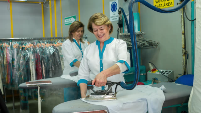 women ironing clothes at a laundry shop - utility room stock videos and b-roll footage