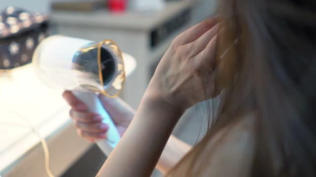 女性はお風呂にドライヤーで髪を乾燥します。 - brown hair点の映像素材/bロール