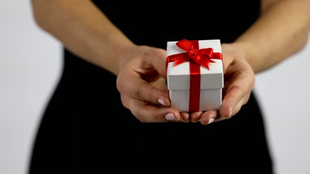 a women is extending a small white gift box with red ribbon towards the camera. - birthday gift stock videos & royalty-free footage