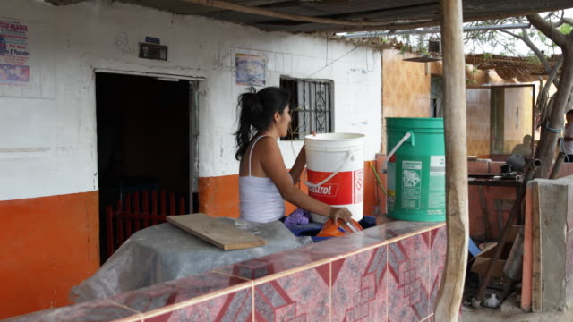 vídeos y material grabado en eventos de stock de a women is filling water into buckets in front of a house in la tortuga peru - océano pacífico sur