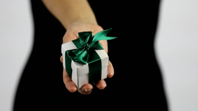 A women is showing a small white gift box with green ribbon towards the camera.
