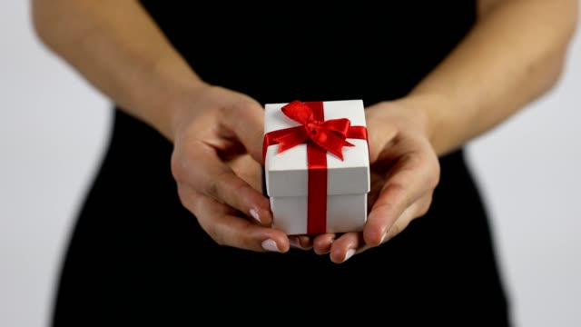 a women is showing a small white gift box with red ribbon towards the camera. - wrapped stock videos & royalty-free footage