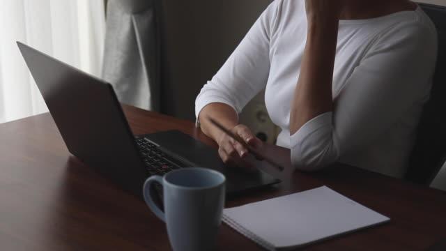 女性は彼女のペンを振り回しながら座っていると彼女のラップトップの前に考えることです。 - ブランコ点の映像素材/bロール