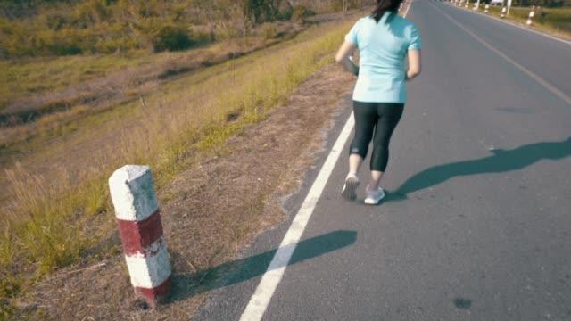 vídeos y material grabado en eventos de stock de las mujeres que trotar y ver el tiempo que el reloj inteligente. - corredora de footing