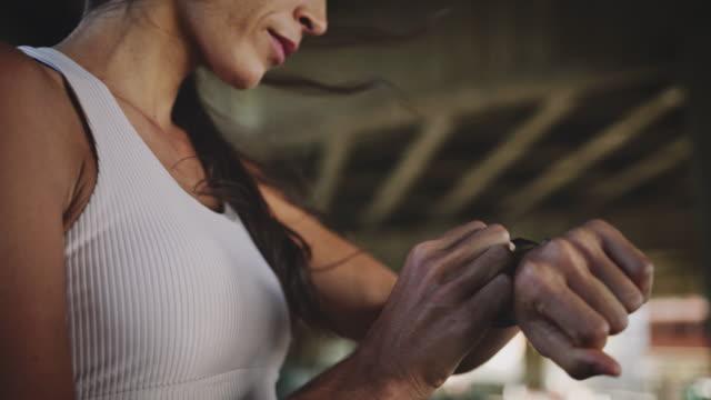 frauen joggen mit blick auf smartwatch - exhaustion stock-videos und b-roll-filmmaterial