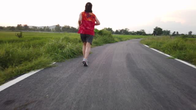 vidéos et rushes de femmes faisant du jogging sur des routes dans les zones rurales en asie du sud-est, thaïlande - joggeuse