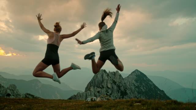 stockvideo's en b-roll-footage met slo mo vrouwen jumping in vreugde op de top van een berg - julian alps