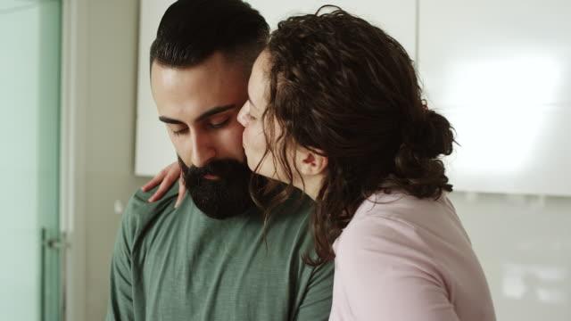 Women kissing men in kitchen
