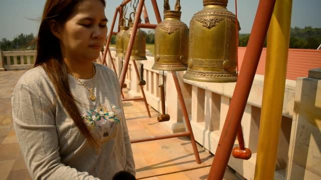 vidéos et rushes de les femmes frappent les cloches au culte. - lieu de culte