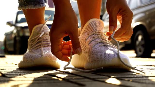 vídeos de stock, filmes e b-roll de mulheres que amarram sapatas do exercício - laço acessório
