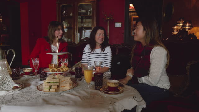 3 women laughing and enjoying a high tea afternoon in melbourne - アフタヌーンティー点の映像素材/bロール