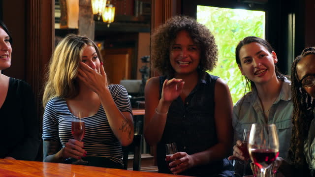 ms women laughing hysterically while friend tells a story in a bar - only women stock videos & royalty-free footage