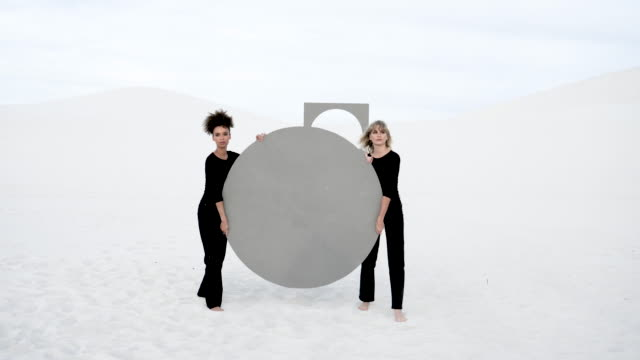 women lift circular portal in desert, medium shot - full length stock videos & royalty-free footage