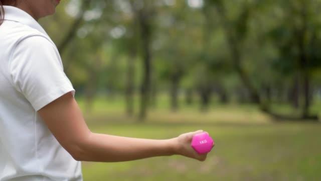 stockvideo's en b-roll-footage met vrouwen gewichtheffen, uit te oefenen op het natuurpark, healty concept. - jogster