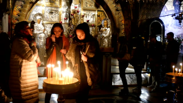women lighting candles in the holy sepulchre church/ jerusalem old city - jerusalem stock videos & royalty-free footage