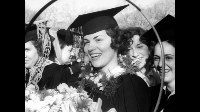 vidéos et rushes de / women lined up in graduation gowns holding hoops and sticks / women begin to race pushing their hoops down the slope to determine marriage order as... - 1930