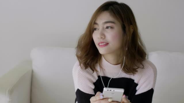 stockvideo's en b-roll-footage met vrouwen luisteren van muziek van podcast - in ear koptelefoon