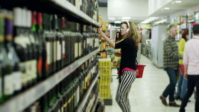 vídeos y material grabado en eventos de stock de mujeres escuchando música en auriculares y buscando buena botella de vino en el supermercado - super slow motion