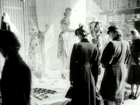 stockvideo's en b-roll-footage met women look at dresses displayed in a shop window 1954 - kleding
