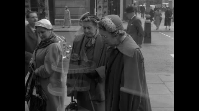 women look at shoe shop window; 1956 - 1956 stock-videos und b-roll-filmmaterial