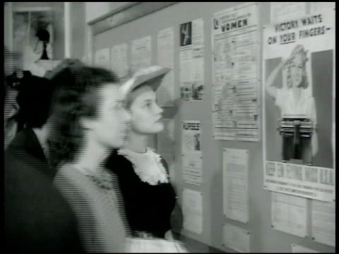 vidéos et rushes de women looking at job postings on hallway bulletin board ws people in many lines in room clerks handing out paperwork from divided folders - 1942